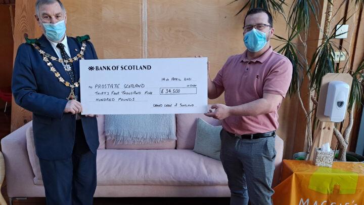 The Grand Master Mason presenting a cheque for £34,500 for Prostate Scotland to Brian Corr